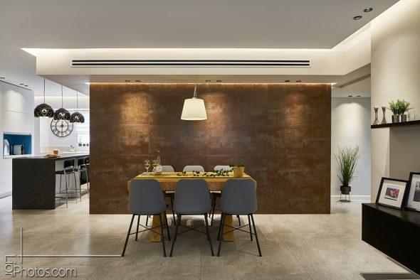 חיפוי גרניט פורצלן דמוי חלודה על קיר פינת האוכל ועל קיר המטבח.