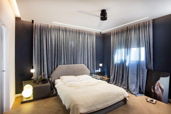 חדר השינה:הנמכת תקרה עם תאורה היקפית, וילונות כהים בגוון הטפט הכחול.