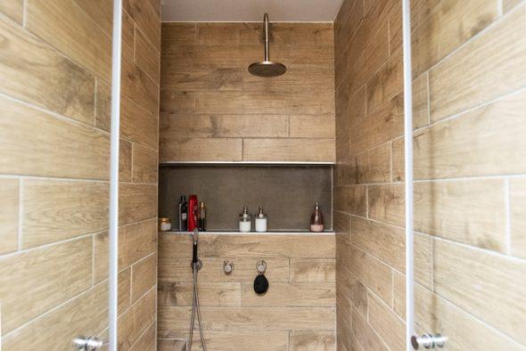 מקלחון ענק עם תכנון נישה לבקבוקי שמפו , וספסל לישיבה.