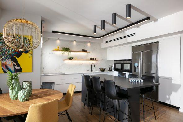 משטח שיש למינם מעל קיר מטבח+מדפי עץ עם תאורה סמויה.