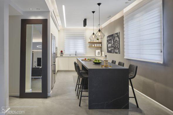 אי ממשטח גרניט שחור בולט על רקע המטבח ההיקפי הלבן.
